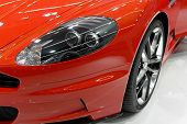 stock photo of headlight  - Headlight and rim of an orange sports car - JPG
