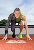 Conceptual image of an athlete (sprinter) ready to start a business career. Performance in business