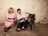 stock photo of queer  - Laughing friends sitting on the floor with funny dog - JPG