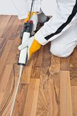 pic of hermetic  - Construction worker in white coveralls applying silicone sealant gun in spaces of old wooden floor - JPG