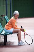 pic of senior-citizen  - Active senior relaxing on the tennis court - JPG