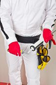 stock photo of mortar-joint  - Worker with red gloves and white suit cuts cap sealant silicon before applying it in corners of bathroom for waterproofing and hygiene - JPG