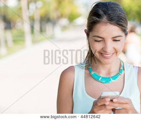 Woman texting from her mobile phone outdoors