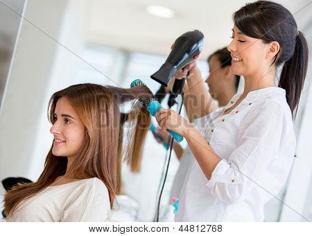 Stylist Trocknen Haare eines weiblichen Kunden in den Schönheitssalon