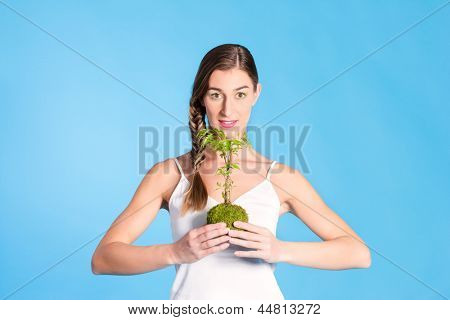 Young woman holding symbolically a small tree, a symbol for the protection and the care of our environment, the woods and world