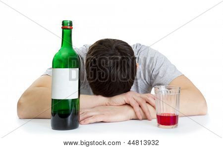 the young man sleeping at a table and a bottle with wine