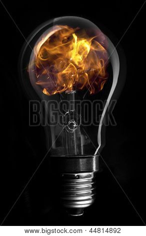 Flame inside light bulb on black background