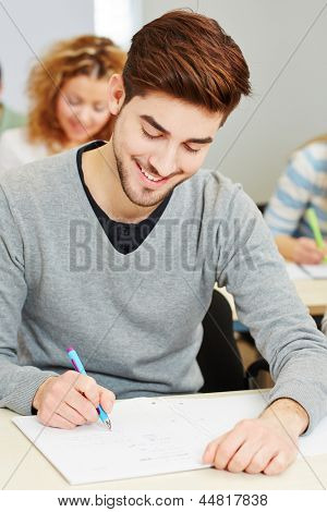 Young mann taking exam in university class