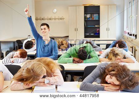Sleeping students and diligent pupil in a school classroom