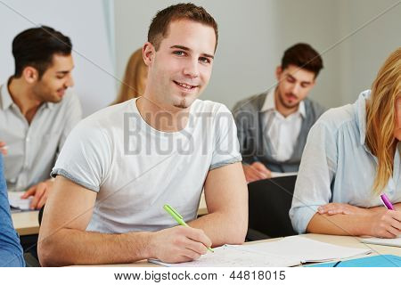 Happy student studying in a course of a college