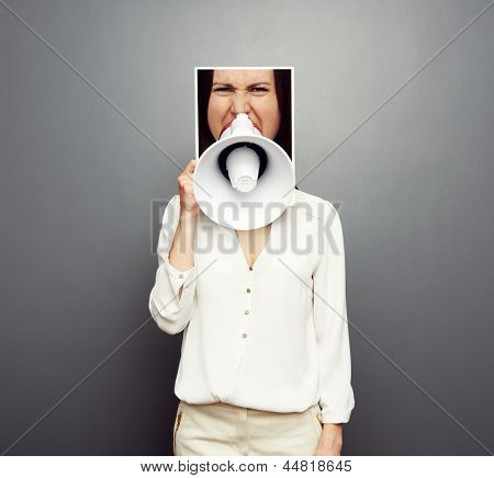 concept photo of young female screaming in megaphone over dark background