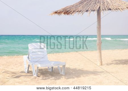Beach Lounge On The Sandy Beach Under Thatched Sunshade