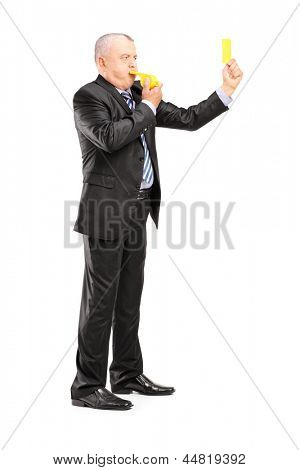 Full length portrait of a mature businessman blowing a whistle and showing a yellow card, isolated on white background
