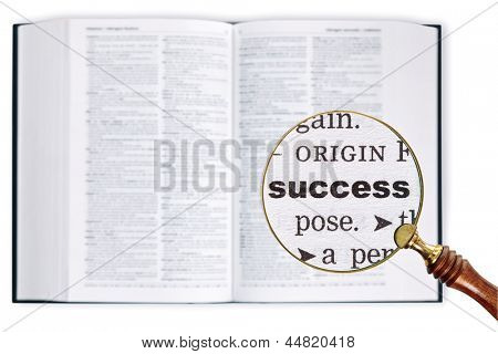 A magnifying glass held over a dictionary looking at the word Success enlarged