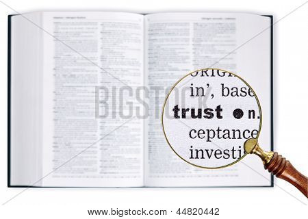A magnifying glass held over a dictionary looking at the word TRUST enlarged
