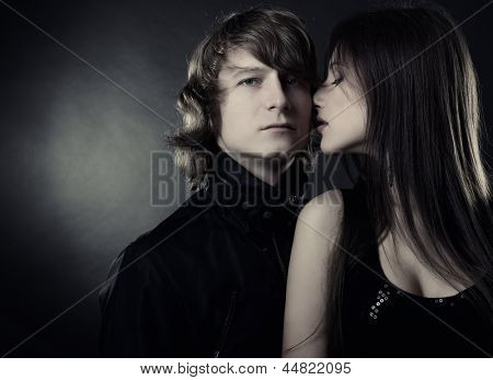 Sexy passion couple, beautiful young woman and man in love posing in studio, over black