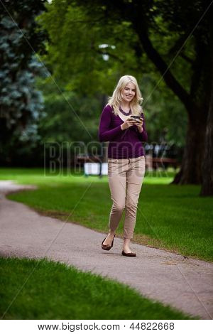 Woman in park looking at camera using cell phone
