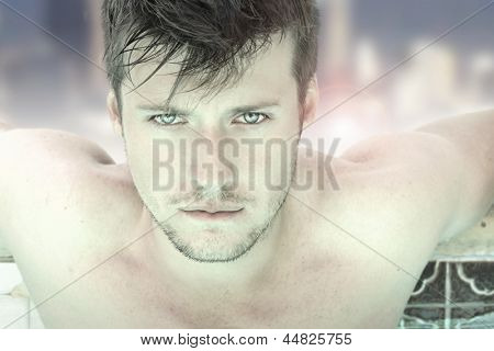 Close-up fashion portrait of a gorgeous male model relaxing in luxurious swimming pool