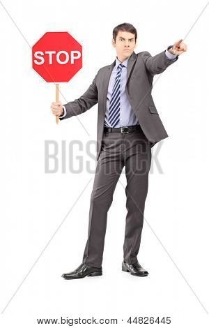 Full length portrait of a man in suit holding a stop sign, isolated on white background