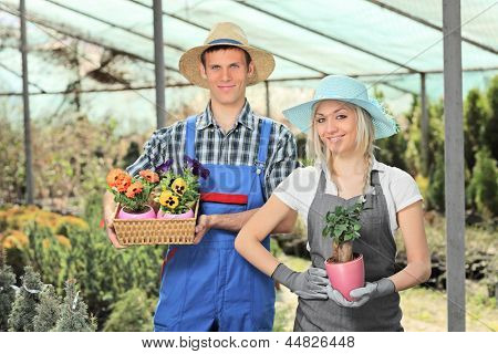 Female and male gardeners holding flower pots and posing in a hothouse