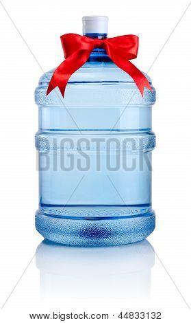 Botella grande de agua atado con un lazo de cinta de raso rojo aislado sobre fondo blanco