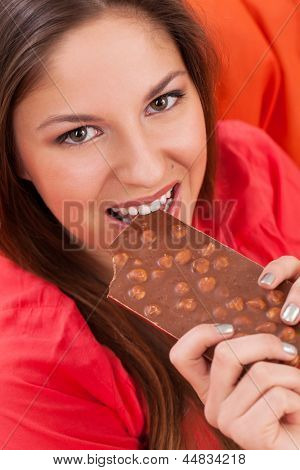 Beautiful woman eating a chocolate sitting in the orange chair