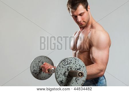 Young handsome bodybuilder with naked torso and barbell isolated over grey background