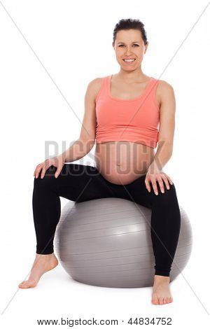 Beautiful pregnant woman sitting on a ball isolated over white background
