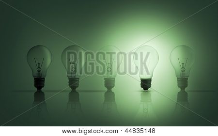 Light bulbs in a row with one lit up against green background