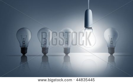 Five light bulbs in a row with one lit up against grey background