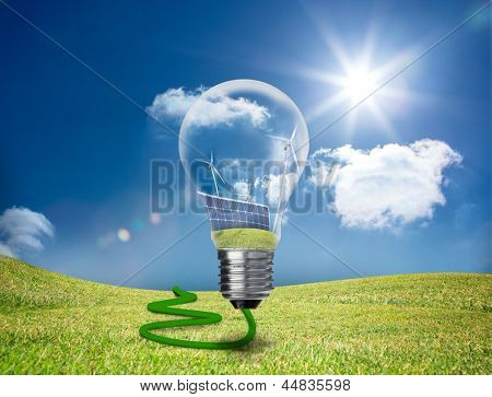 Light bulb showing solar panels and turbines floating in a green field in the sunshine