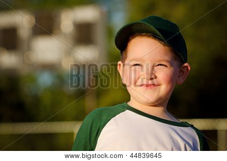 Portrait of child baseball player on field in front of scoreboard