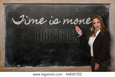Teacher Showing Time Is Money On Blackboard