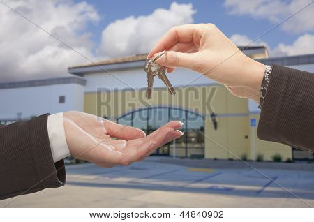 Real Estate Agent Handing Over the Keys in Front of Vacant Business Office.