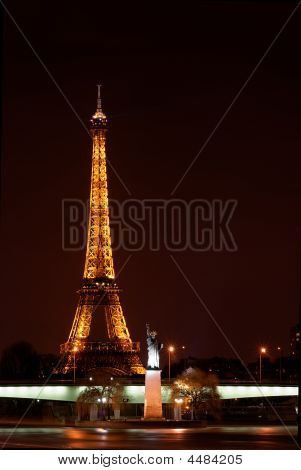 Statue Of Liberty Near The Eiffel Tower In Paris By Night
