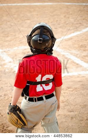 Child playing catcher during organized league baseball game