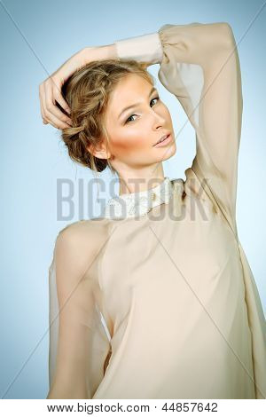 Charming fashionable model in elegant light dress posing at studio.