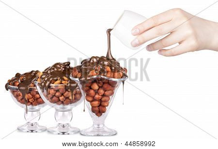 Chocolate Flowing Over Nuts In A Glass  Isolated