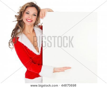 Female Santa pointing at an empty banner, isolated over a white background.