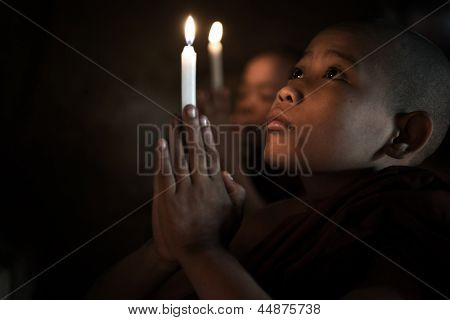 Little monks praying with candlelight