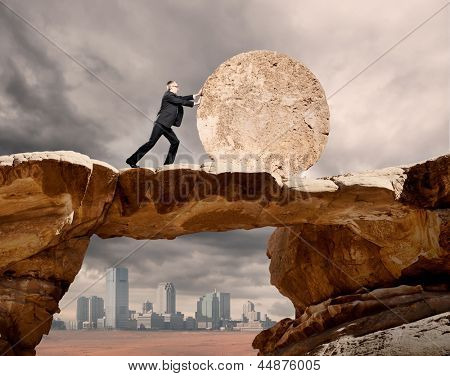 businessman pushing a stone wheel
