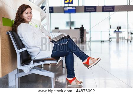 Smiling Woman With Devices Sitting In Airport Lounge