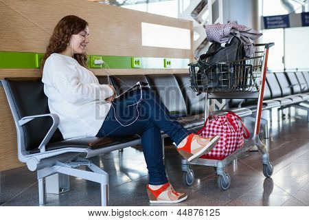 Woman Spending Time With Tablet Pc In Airport Lounge With Luggage Hand-cart