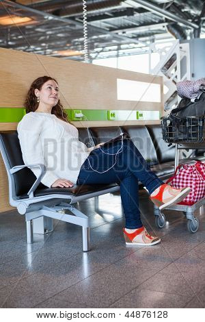 Woman Dreaming With Tablet Pc In Airport Lounge With Luggage Hand-cart