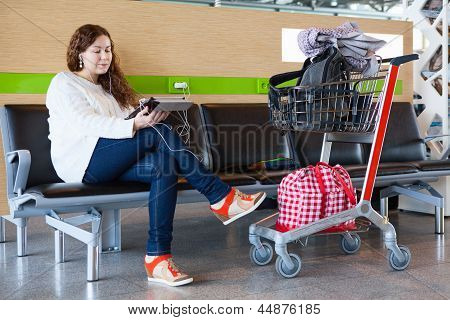 Woman Looking At Tablet Pc In Airport Lounge With Luggage Hand-cart