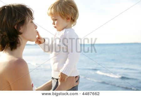 Mother And Blond Son Playing On The Beach