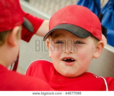 Portrait of happy child in dugout before baseball game