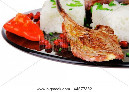 meat food: ribs on black with rice garnish and tomatoes on black over white background