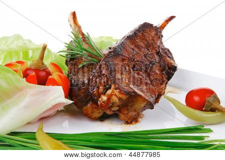savory plate: grilled ribs on white plate with chives, red hot peppers lettuce isolated white background