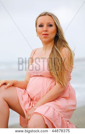 Portrait of a young beautiful blond pregnant woman at beach . on sea background.